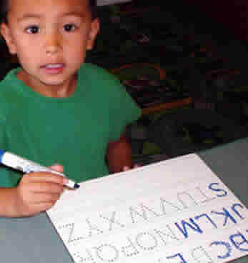 child at Woolly Mammoth Childcare & Pre-School learning to write